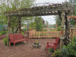 Arbor & red benches - view of perennial & veggie gardens